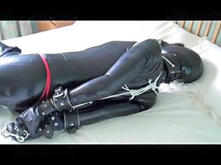 In this second part of the video Karina is still wearing a latex catsuit leather posture collar thigh high boots and open faced hood over which we have fitted a rubber gasmask Watch as karina continues to struggle At one point she almost escapes