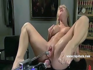 Busty blonde sitting on a desk squirts after being pumped by toys