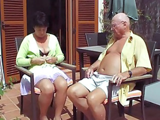 Mature takes her top off under the sun