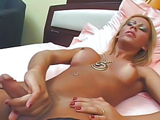 Shemale hottie plays with her cock while wearing leather boots in bed