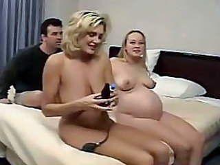 Two pregnant females are having some nice time together on the bed