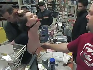 Young redhead is gagged and a dildo is forced into her in sexy shop.