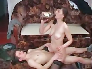 Mature drinks and rides a young cock