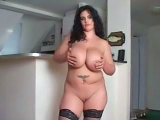 Big busty brunette BBW Tristal puts on a striptease and shows it all