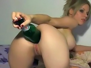 Crazy blonde uses the big end of a bottle to stick in her ass
