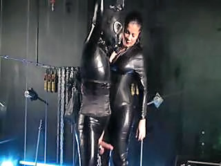 Wrapped On Latex Garb, A Nasty Mistress Tugs On A Male Slave's Cock