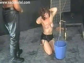 Beautiful slave with her tits tied together is hit with a whip in a dungeon