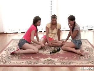 Luscious Teens Are Playing Spin The Bottle On A Rug In The Living Room