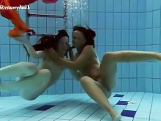 Two beautiful girls swim in a difficulty empty tubes