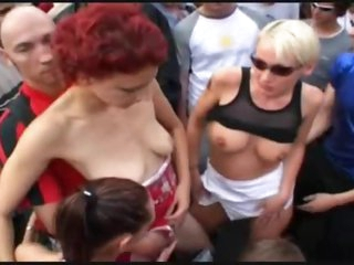 Chicks dance naked in a big crowd outdoors