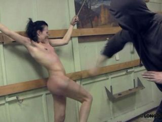 Hands are stretched in a crucifiction style. The lonely pigtail girl has to stand a brutal breast whipping.
