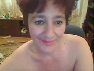 Mature brunette is on her home webcam posing and rubbing her pussy