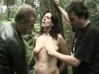 Horny slave is tied to a tree and fucked with a dildo and...