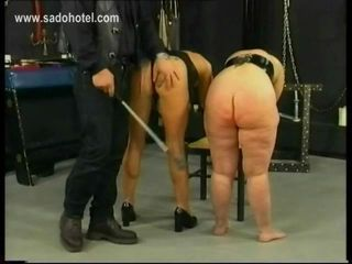 Two german slaves gets spanked on their butts by master in a dungeon