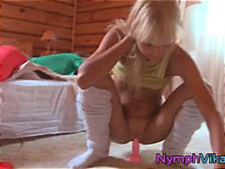 Sexy blonde teen uses a pink dildo to masturbate on the floor