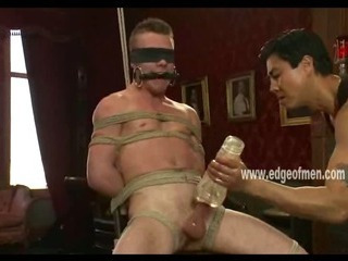 Tattooed hunk is tied up plus gagged measurement a muscular  guy jerks him off forcefully
