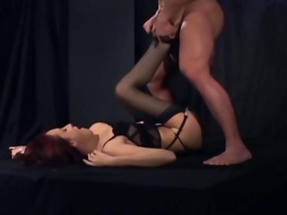 Pretty redhead gives a footjob in sheer stockings