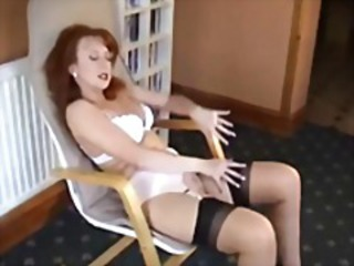 Redhead in lingerie is posing and rubbing her horny pussy