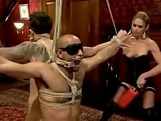 Naughty leather clothed mistress strikes strapped male slaves