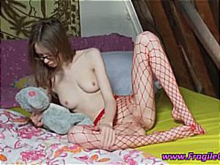 Brunette teen in fishnets is posing and showing her pussy